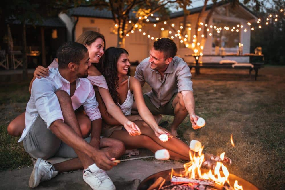 friends sitting around a fire pit outdoors
